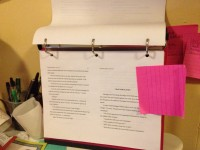 Photo of three-ring binder with manuscript pages inside. Binder is propped up sideways and open to inner pages of manuscript as pages were printed landscape with two manuscript pages per printed page.