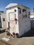 Marie Laveau's tomb in St. Louis Cemetery Number 1 in New Orleans. It is whitewashed and covered in graffiti, mainly groups of three x's, to invoke her assistance.