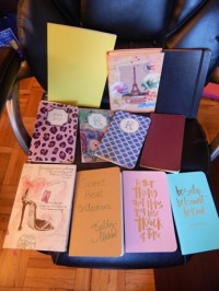 Picture of 11 notebooks that are part of my notebook collection. They include a black Moleskine notebook, two other Moleskine-brand notebooks, customized notebooks from May Designs, a Yoobi notebook from Target, and two blank notebooks with pretty, travel-related covers that I got at Staples.