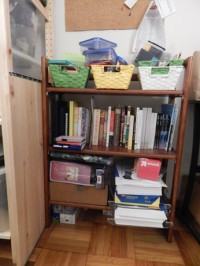 View of the 3-shelf bookcase with my writing-related materials. The top shelf has 3 woven paper bins filled with office supplies side-by-side. The middle shelf has my research books, author copies of the anthologies I have been published in, and my notebook collection. The bottom shelf is split between a two-shelf plastic holder filled with reams of office paper (with a box of snack baggies sitting on top of those) and containers filled with promotional materials.