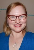 Headshot of Kelly Maher. She is wearing a blue v-neck t-shirt, has strawberry blonde hair, and is wearing cat's eye glasses with a red top rims and tortoise shell lower rims.